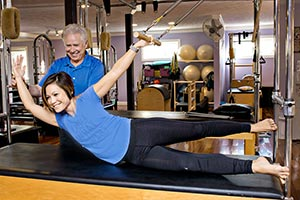 George teaches Charlyn the Teaser on the Cadillac to strengthen the abdominals.